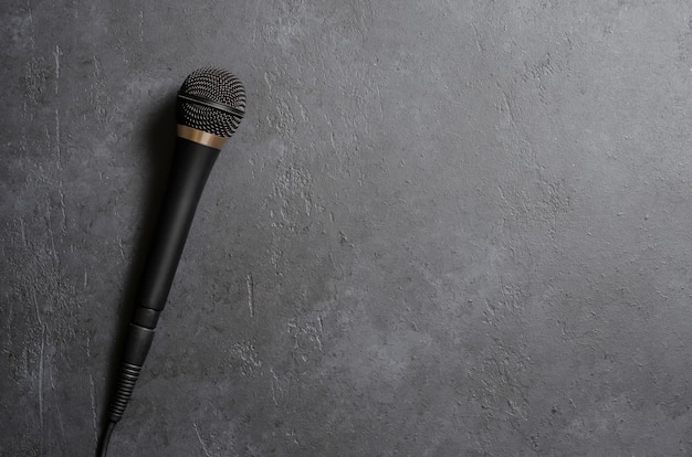 暗いコンクリートのテーブルに黒いマイク。ボーカル、インタビュー、レポーティング用の機器。コピースペース