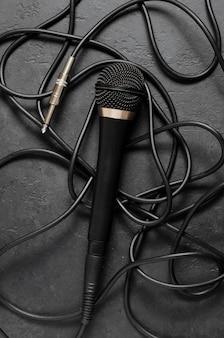 暗いコンクリートのテーブルに黒いマイク。ボーカル、インタビュー、またはレポーティング用の機器