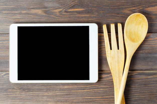 タブレットコンピューターと木のスプーンと茶色の背景にフォーク。