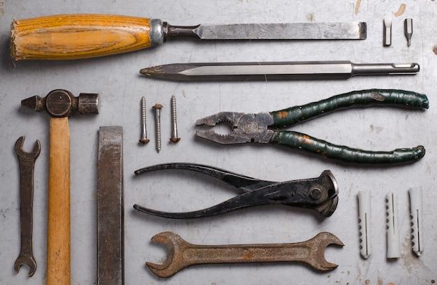 Набор ручных старых инструментов на сером фоне