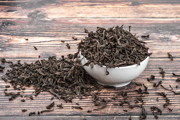 乾燥茶は、木の板のテーブルの上のセラミックカップに注がれます。