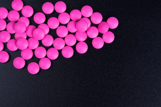 ピンクの錠剤が黒の背景に散在しています
