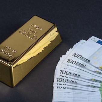 黒の背景にユーロの現金と金の延べ棒。紙幣。お金。ビル。インゴット。地金。