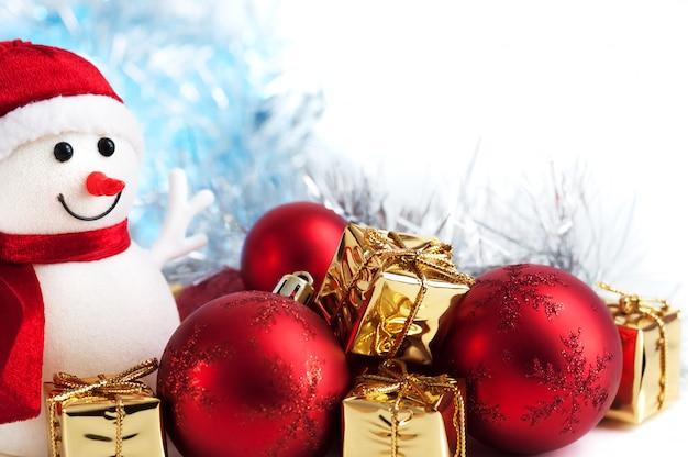 Счастливого рождества, нового года, снеговик, подарки в золотых коробках и красные шары на фоне синего и белого боке.