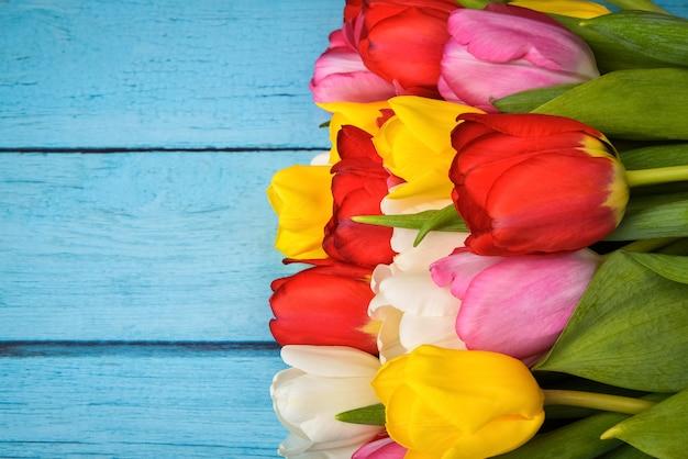 Яркий букет из разноцветных тюльпанов крупным планом на деревянных досках синего цвета.