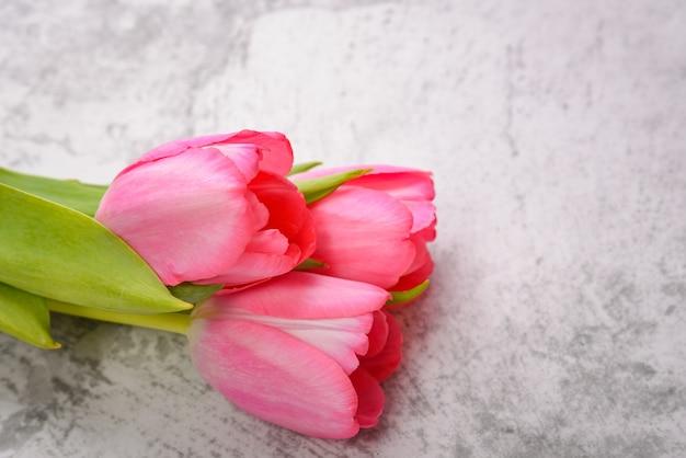 明るい灰色のテーブルの上にあるチューリップは、明るく新鮮なピンク色です。