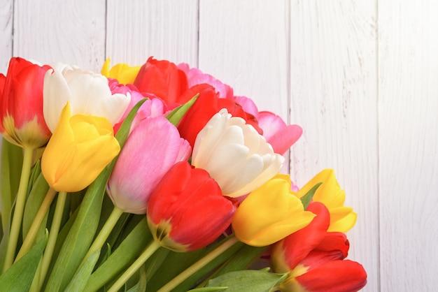 白い木の板に新鮮で明るい、マルチカラーのチューリップの花束。