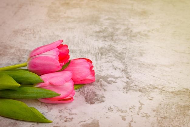 チューリップは明るい、新鮮、ピンク、明るい灰色のテーブルのクローズアップ。