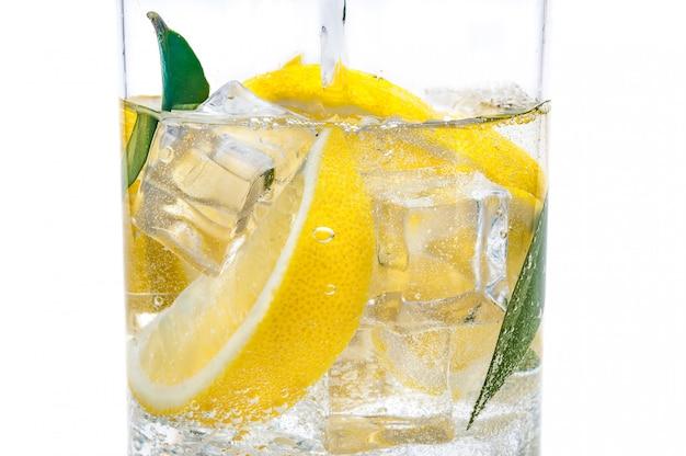 水差しの中には氷、新鮮なジューシーな黄色いレモンの小葉および透明な水があります。