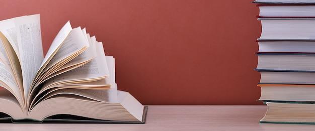本は開いていて、本の山の近くのテーブルに横たわっています