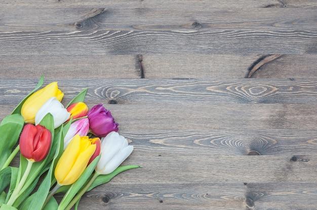 木の背景の角に色とりどりのチューリップの花束。