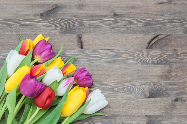 木製の背景にチューリップの大きい春の花束。