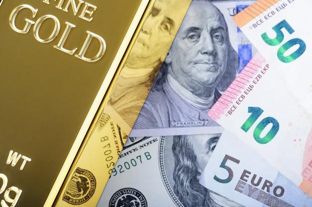 ドルとユーロ紙幣の背景に金の金属インゴット地金。