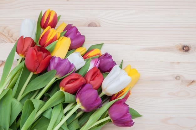 明るい色の木を背景にした、画像の左下隅にある鮮やかな色の春のチューリップの大きな花束。