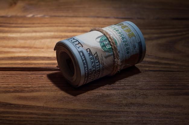 ドルのロールは光線で照らされた暗闇の中で木製の織り目加工のテーブルの上にあります。