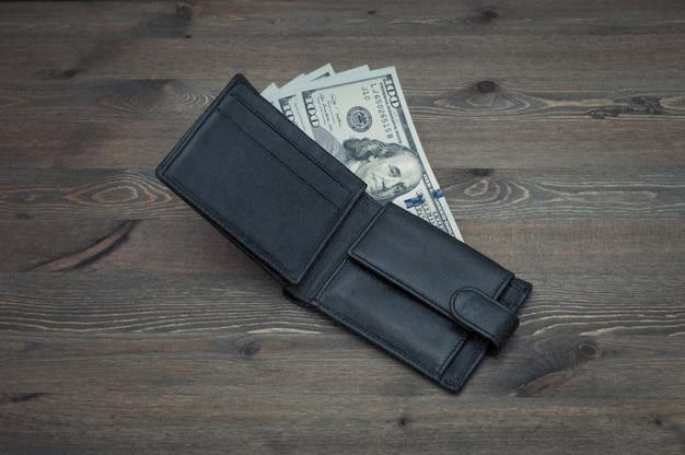 Раскрытый черный кошелек с счетами сто долларов на деревянном столе.