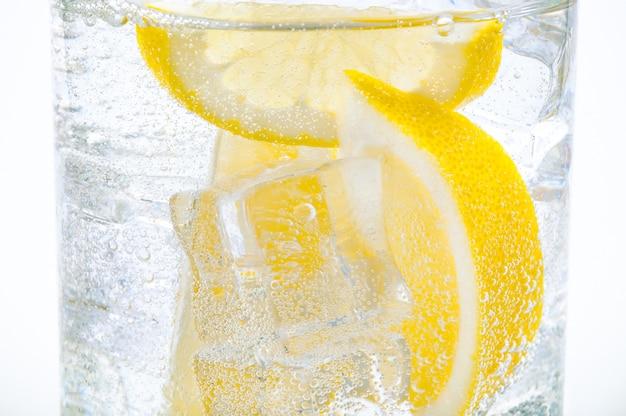 グラスに氷、レモンスライス、そして透明な水が入っています。