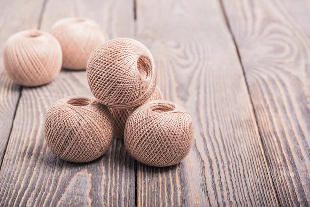 Шарики нити пряжи для вязания на деревянном фоне.