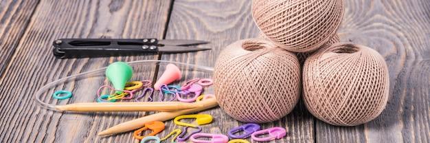 Клубки пряжи, спицы, ножницы и зажимы на деревянных фоне.