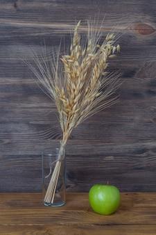 木の板の背景に花瓶に小麦と大麦のスパイク。