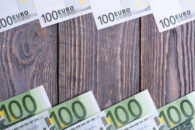 ユーロ紙幣は、木製の背景でフレームをうそをつきます。