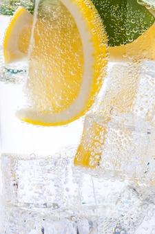 Освежающий, холодный, вкусный, сладкий лимонад с дольками лимона и кубиками льда.