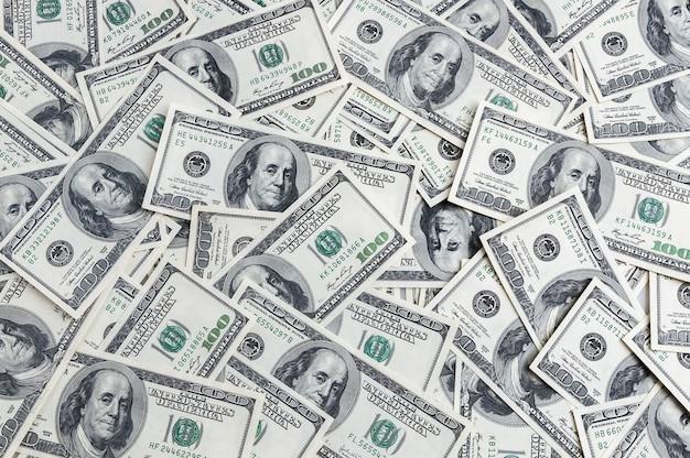 Фон из сотен долларов, разбросанных по столу.