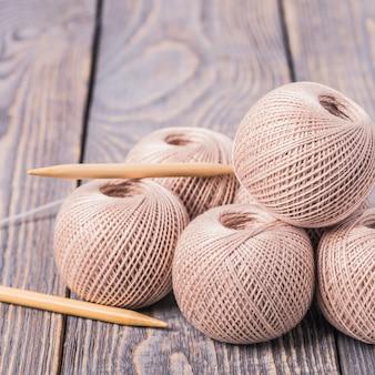 Шарики пряжи и вязальных спиц для вязания на деревянном фоне.