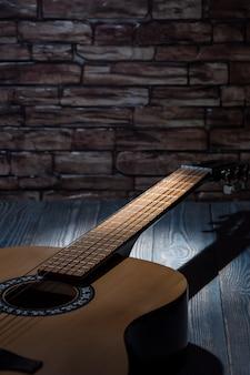 光のビームは、暗闇の中で横になっているアコースティックギターを照らします。