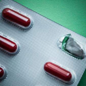 Блистер с темно-красными таблетками на зеленом фоне.
