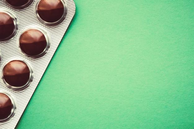 Волдырь с коричневой таблетки на зеленом фоне.