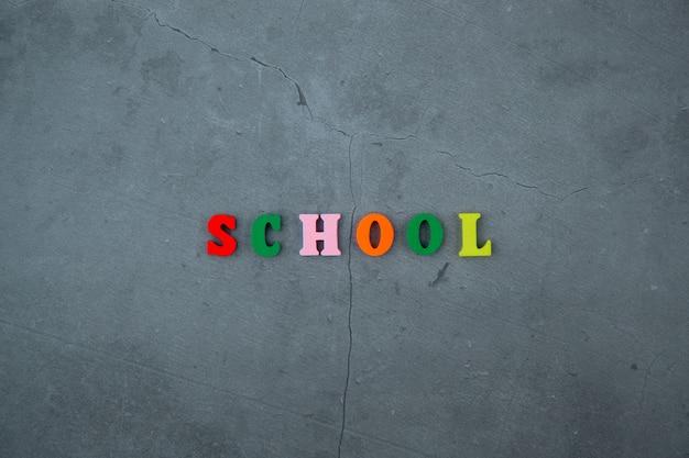 色とりどりの「学校」という言葉は、灰色の漆喰壁に木製の文字でできています。