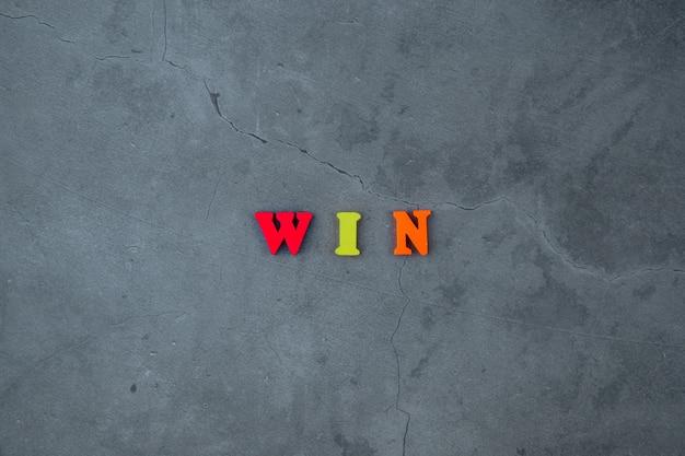 色とりどりの「勝利」という言葉は、灰色の漆喰壁に木製の文字でできています。