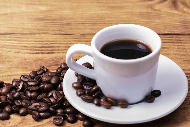 一杯のコーヒーと散らばったコーヒー豆。レイアウト。平干し。コーヒー豆。