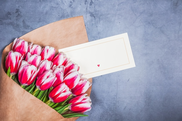 Букет из красных тюльпанов на праздник женский день и день святого валентина на фоне серой фактурной стеной.