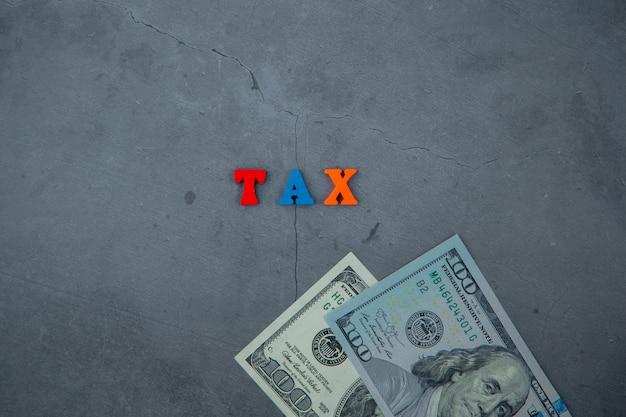 色とりどりの税の単語は灰色の漆喰壁に木製の文字で作られています。