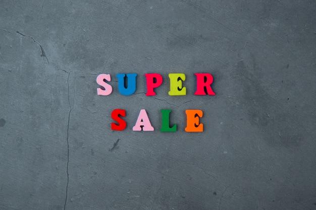 色とりどりのスーパーセールの単語は灰色の漆喰壁に木製の文字で作られています