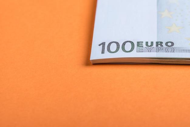 ピンクとオレンジ色の背景にユーロの現金