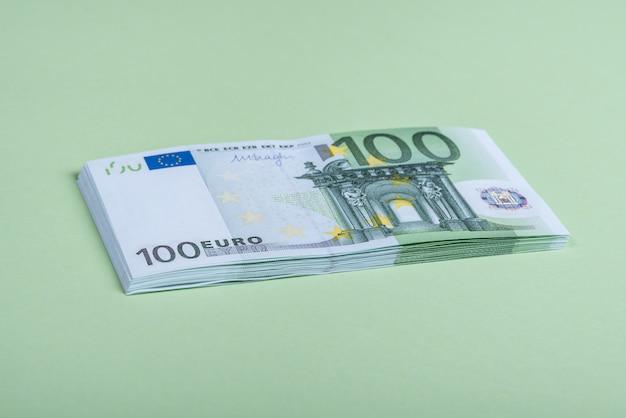 緑の背景にユーロの現金