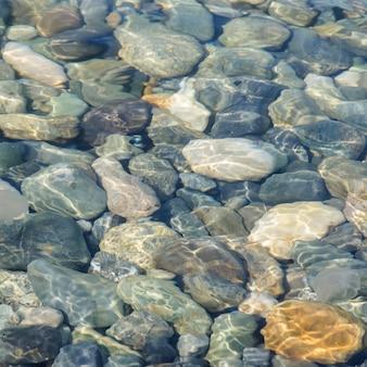 水の下で海の色の石の背景