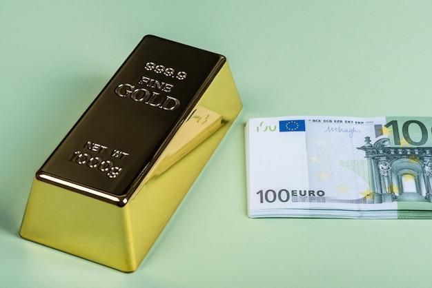 緑の背景にユーロの現金と金の延べ棒