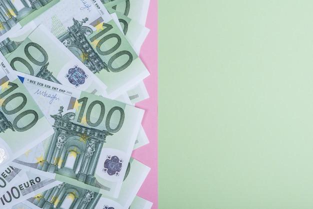 ピンクと緑の背景にユーロの現金。ユーロマネー紙幣。ユーロマネー。ユーロ紙幣。