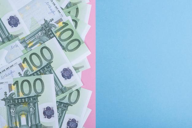 青とピンクの背景にユーロの現金。ユーロマネー紙幣。ユーロマネー。ユーロ紙幣。