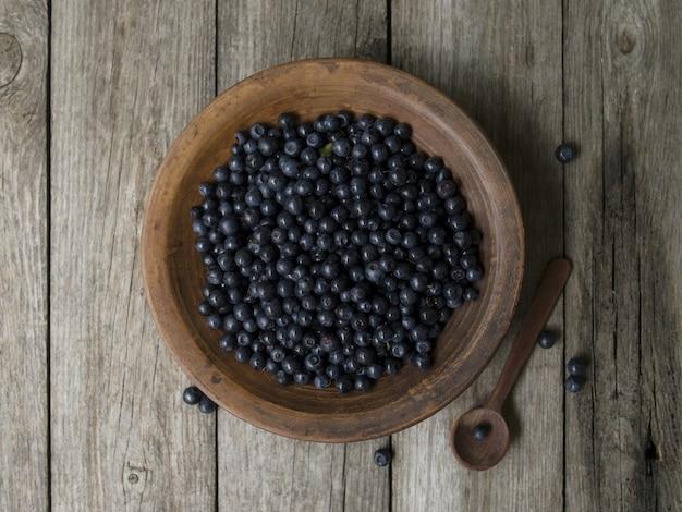 古い木製のテーブルの上のブルーベリーと粘土ボウル。採れたての果実。ブルーベリー抗酸化スーパーフード、健康的な食事のためのコンセプト。