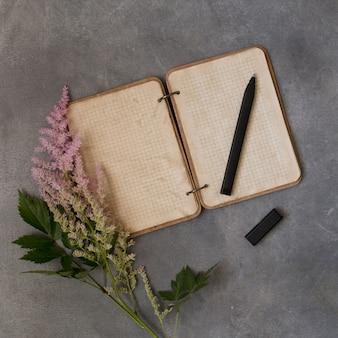 トップビューフラットピンクの花、色とりどりのアスティルバ、灰色の背景上のモックアップで空のメモ帳を置きます。テキストスペースビンテージ。結婚式や誕生日の招待状やメッセージの概念