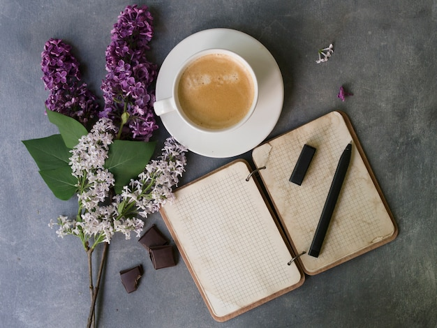 グレーのテーブルの上のコーヒー、ノートブックとライラックの花。女性作業机。