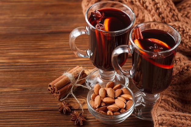 冬水平グリューワインのバナー。ホット赤ワインと木製の背景にスパイスグラス。