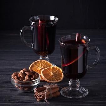 グリューワインのバナー。ホット赤ワインと暗い背景にスパイスのグラス。モダンなダークムードスタイル。
