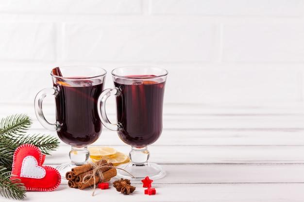 冬水平グリューワインのバナー。ホット赤ワインとスパイスをグラス、木、フェルトの装飾