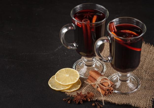 グリューワインのバナー。ホット赤ワインと暗い背景にスパイスのグラス。